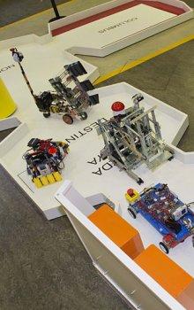 Všech sedm soutěžních robotů na ploše představující Mezinárodní kosmickou stanici ISS, robot českého týmu úplně vzadu v modulu Destiny.