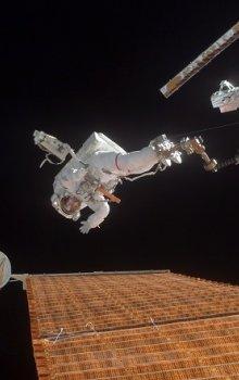U.S. astronaut Scott E. Parazynski repairing photovoltaic panel on ISS.
